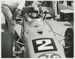 Mario Andretti in car talking to crew member
