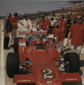A. J. Foyt and crew members beside car in pit road