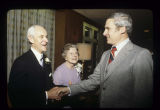 Alexander M. and Rosemary Bracken greeted by a guest at Alexander M. Bracken's retirement dinner