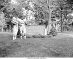 Two football players standing next to Ball State University sign